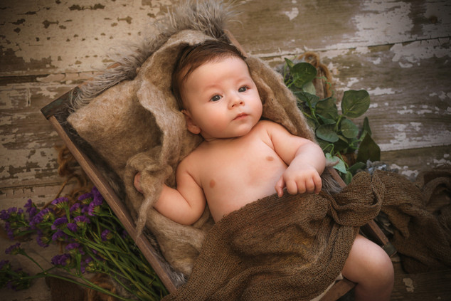 gorgeous baby boy laying in brown wooden crate with a brown blanket over him