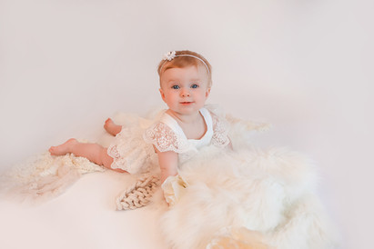 smiling baby girl wearing a white romper lying on a white fluffy rug at her baby photography session with starspeckled hearts photography