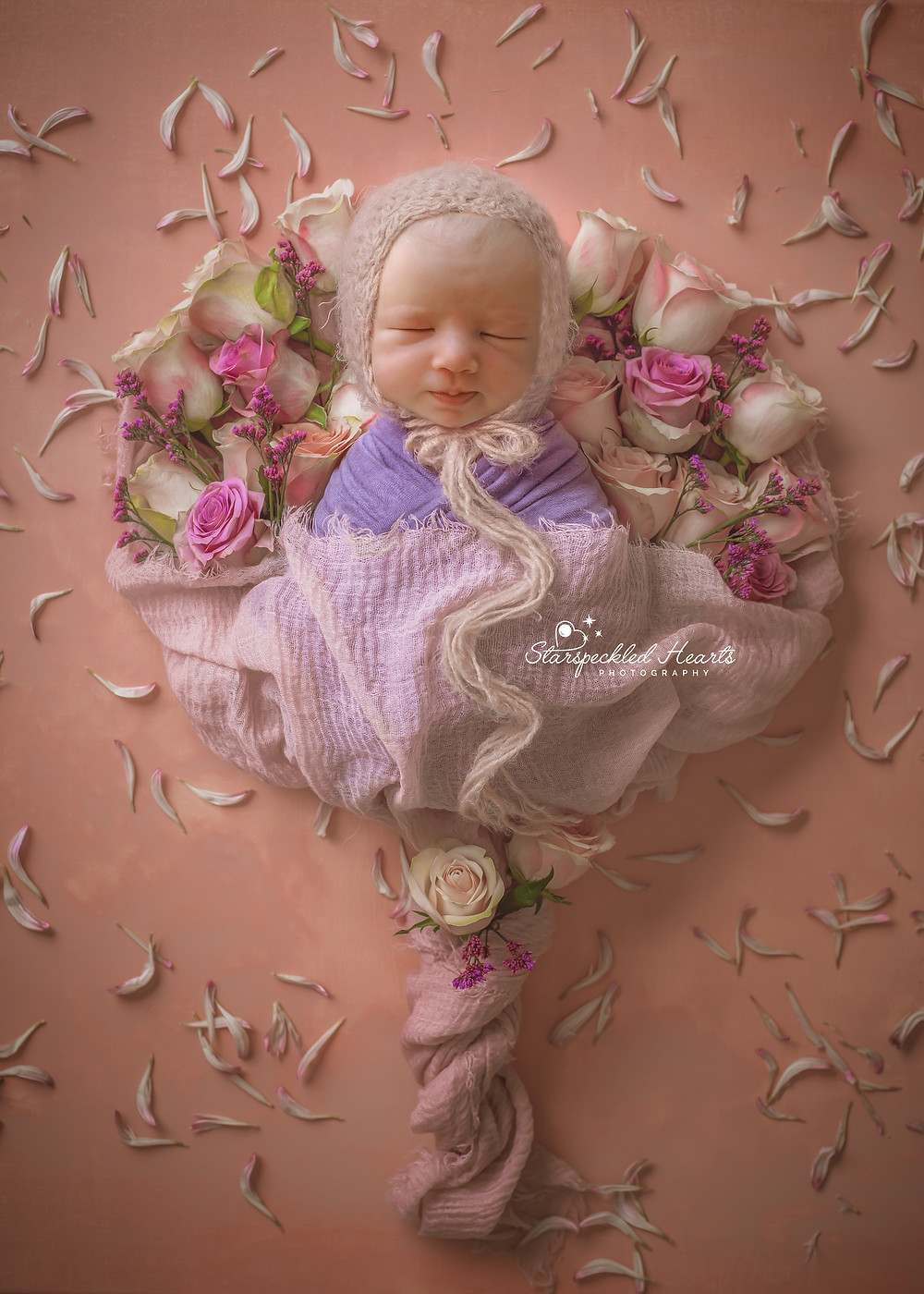 gorgeous sleeping baby girl laying in a bouquet arrangement of flowers on a pink background