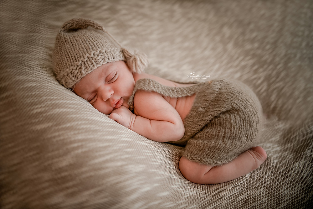 newborn baby boy curled up on his tummy wearing a matching brown romper and hat set