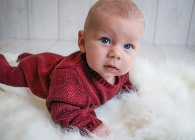 little boy with big blue eyes laying on tummy