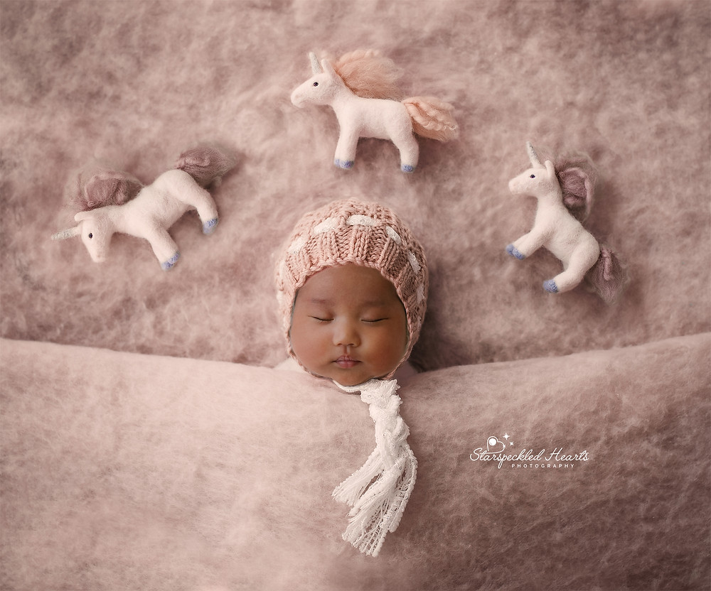 gorgeous sleeping newborn girl wearing a pink knitted bonnet, laying under a felted pink blanket with three stuffed unicorns over her head