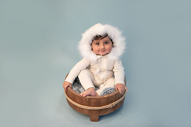 smiling baby boy wearing a white romper with a furry hood sitting in a wooden basket on a blue background for his sitter session with starspeckled hearts photography