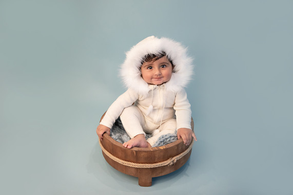 cute baby boy wearing a white romper with a fluffy white hood sitting in a wooden bowl on a blue background for his baby photography session with starspeckled hearts photography