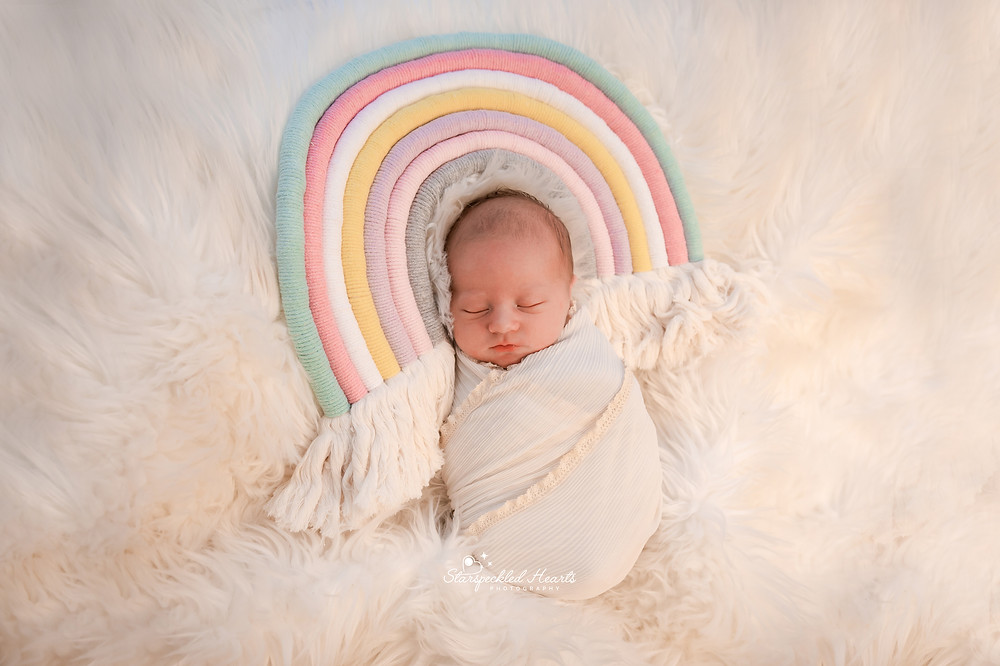 newborn baby wrapped up with a macrame rainbow over her head, lying on a white fluffy rug