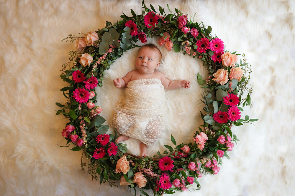 newborn girl laying inside a wreath of red and pink flowers