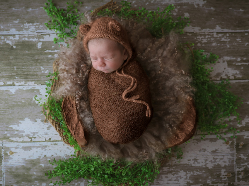 sleeping newborn wearing brown bear bonnet