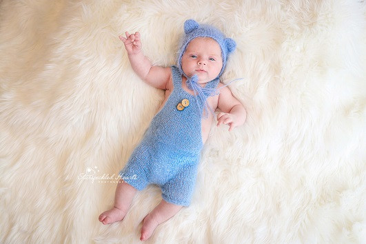 gorgeous baby boy wearing a blue bonnet with ears and a blue knitted romper