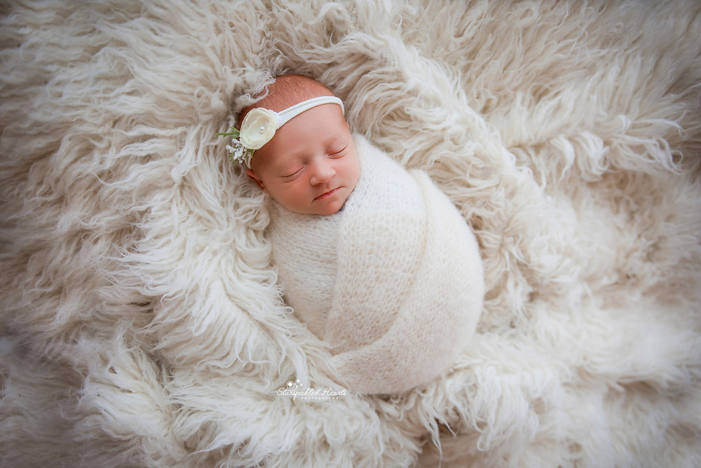 gorgeous newborn baby girl wrapped in white, lying on a large white furry rug