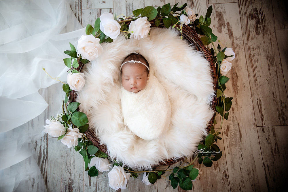 gorgeous newborn baby girl wrapped up, lying in a large wicker basket fast asleep for her newborn photography session