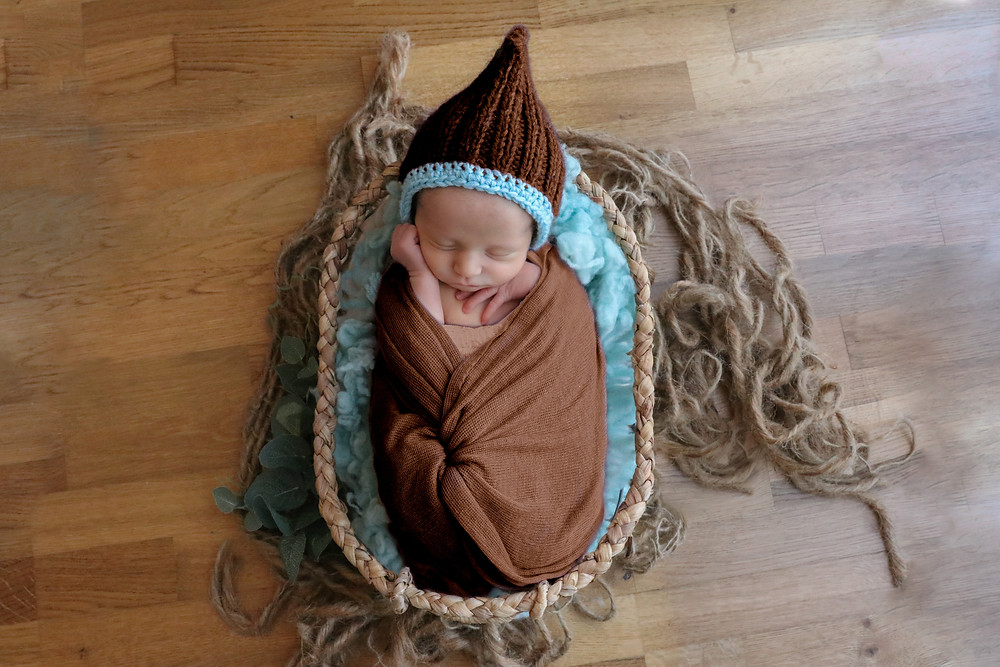 sleepy newborn with hands up around his face, wearing dark brown bonnet with duck egg blue trim and brown wrap, lying in a brown basket with wicker trim
