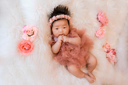adorable baby girl lying on a white fluffy rug for her 100 day milestone session with starspeckled hearts photography