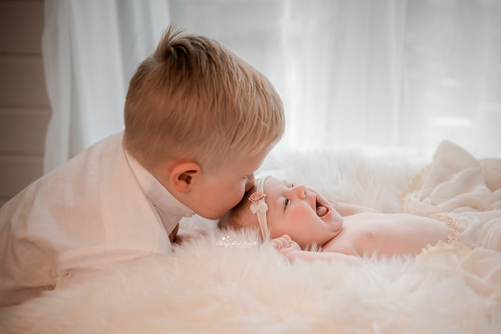 a big brother giving his smiling  baby sister a kiss on the forehead