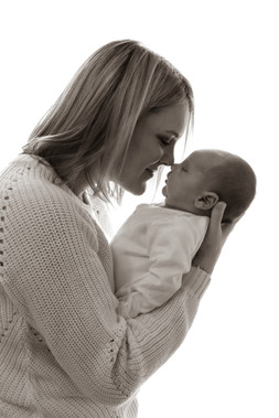 blonde woman touching noses with her newborn son, both wearing all white