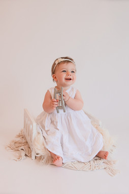 smiling baby girl wearing a white dress sitting on a white fluffy rug with her toy wooden rocking horse at her baby photography session with starspeckled hearts photography