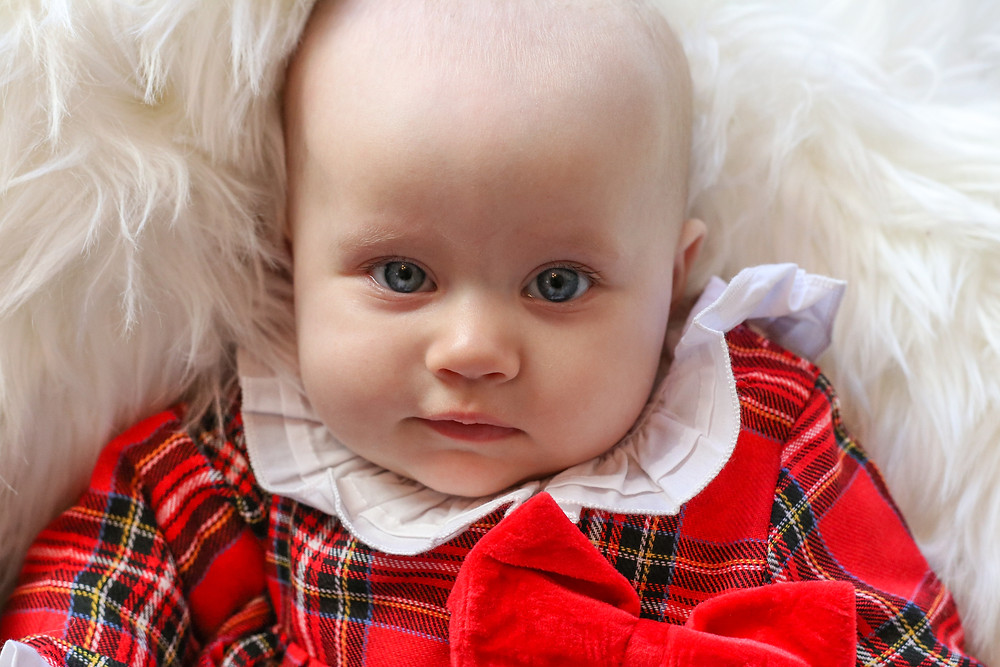 gorgeous baby girl with big blue eyes wearing a red tartan christmas outfit with peter pan collar and a big red bow