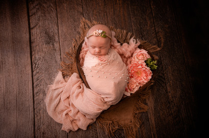 sleeping newborn wrapped in pink, lying in a heartshaped bowl with flowers in for her newborn session in aldershot hampshire