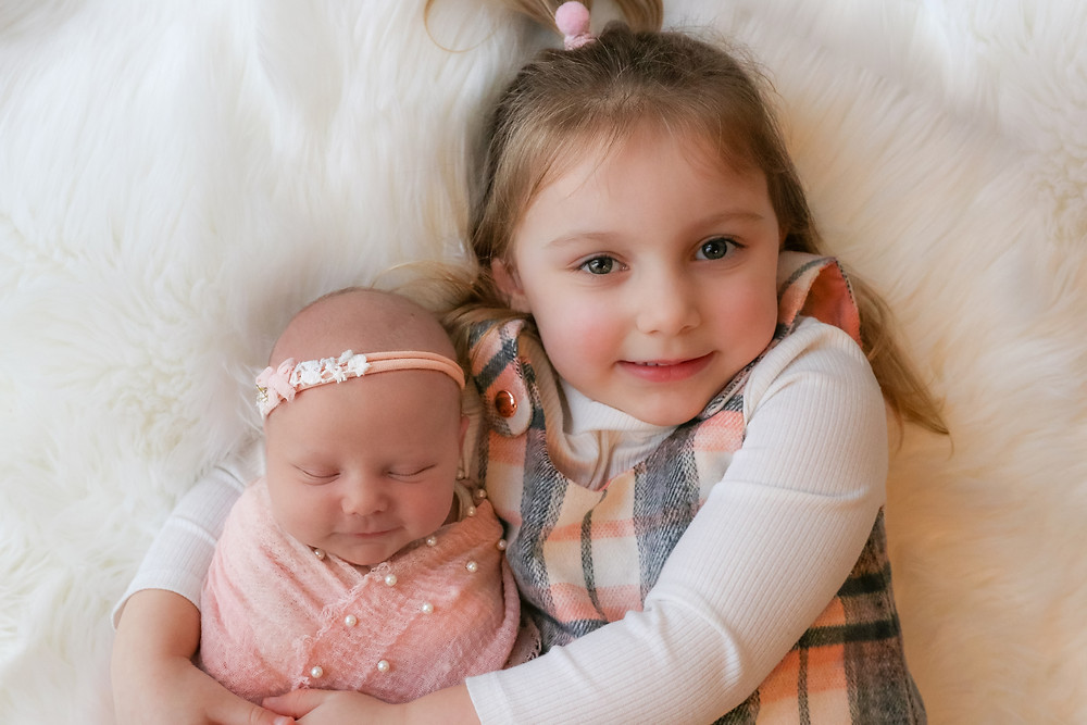 smiling newborn girl laying in big sisters arms