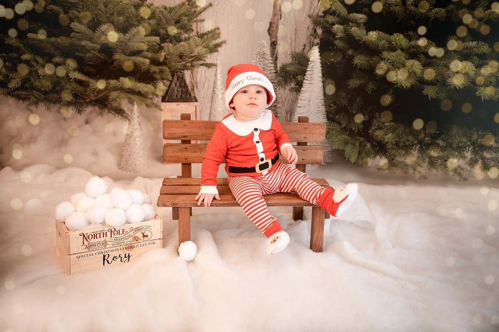 little boy in a santa outfit sitting on a wooden bench on a snowy floor with a christmas backdrop behind him