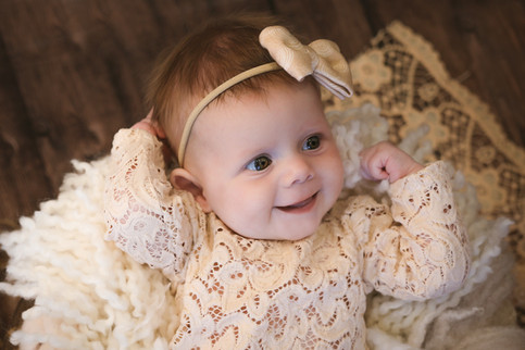 beautiful baby girl wearing a cream lacy romper and matcing bow, laying on a white fluffy layer