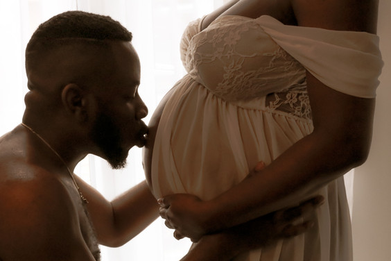pregnant woman wearing a white lacy gown and a man facing each other, man kissing womans pregnant baby bump