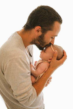 a man cradling his newborn daughter in his arms, giving her a kiss on the forehead