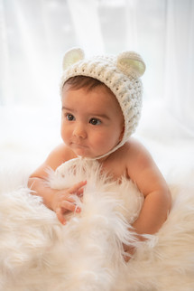 cute baby boy wearing a knitted bear bonnet lying on a white fluffy rug for his little sitter photography session