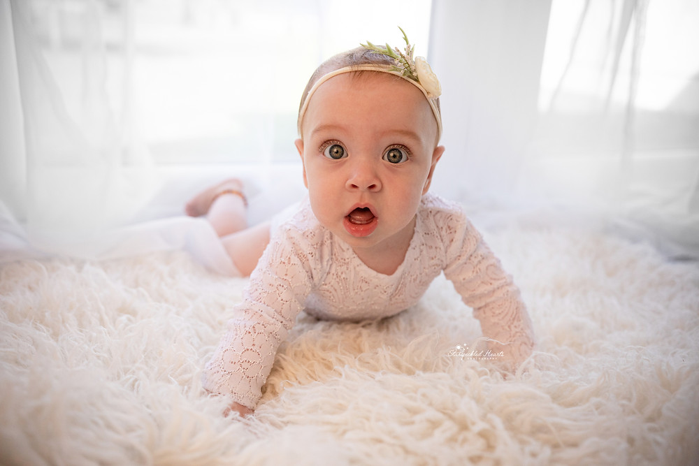beautiful baby girl lying on her tummy on a white fluffy rug, wearing a lace romper