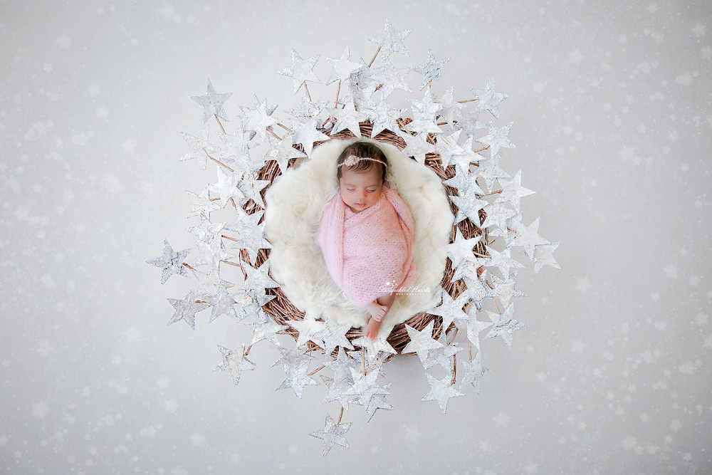 sleeping newborn wrapped in pink, lying in a wicker basket surrounded by large silver stars on a white backdrop with little white stars dotted about