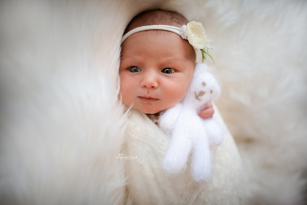 gorgeous baby girl lying on a white furry rug, cuddling a knitted teddy