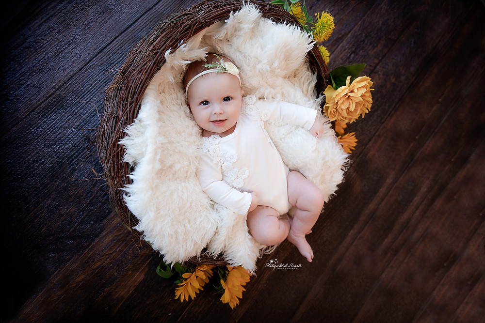 smiling baby girl lying in a wicker basket surrounded by yellow flowers