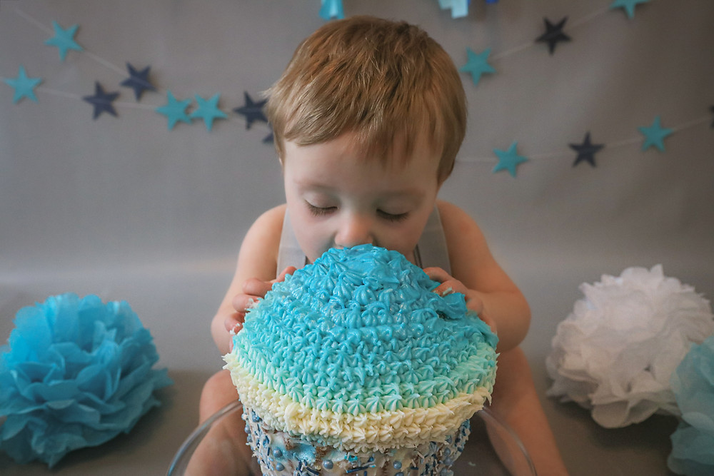 gorgeous little boy diving head first into a large blue cake, with stars and pompoms in the background