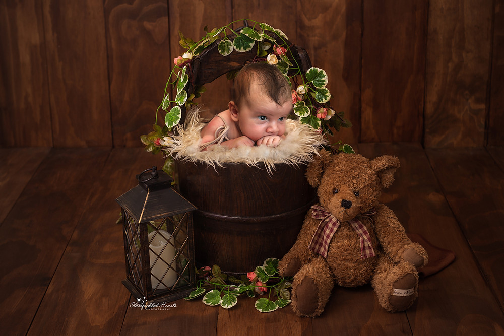 adorable baby boy in a brown wooden bucket, surrounded by greenery and a large teddy