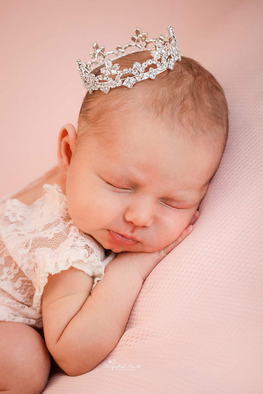 newborn baby girl wearing a white lacy romper and a silver crown on her head on a pink backdrop