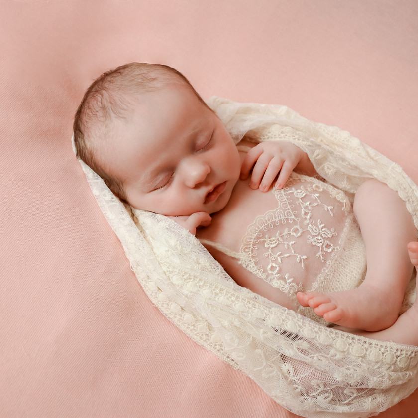 sleeping newborn girl on pink backdrop with lace romper and wrap