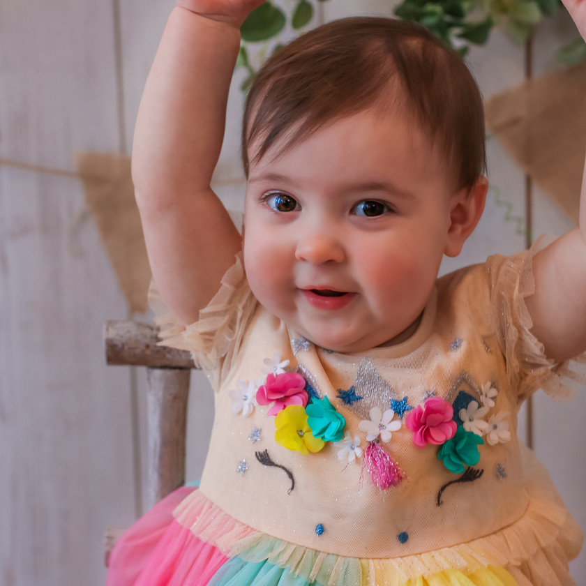 little girl with arms in the air wearing rainbow flower embroidered dress