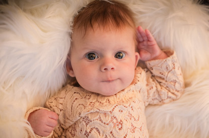 gorgeous baby girl with big blue eyes, wearing a lacy cream romper