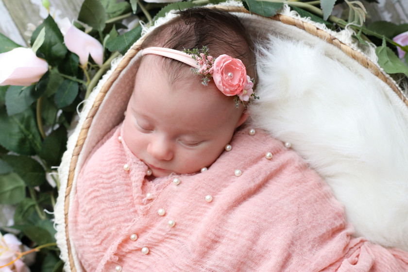 sleeping newborn girl in pink wrapped in pearl embellished cloth
