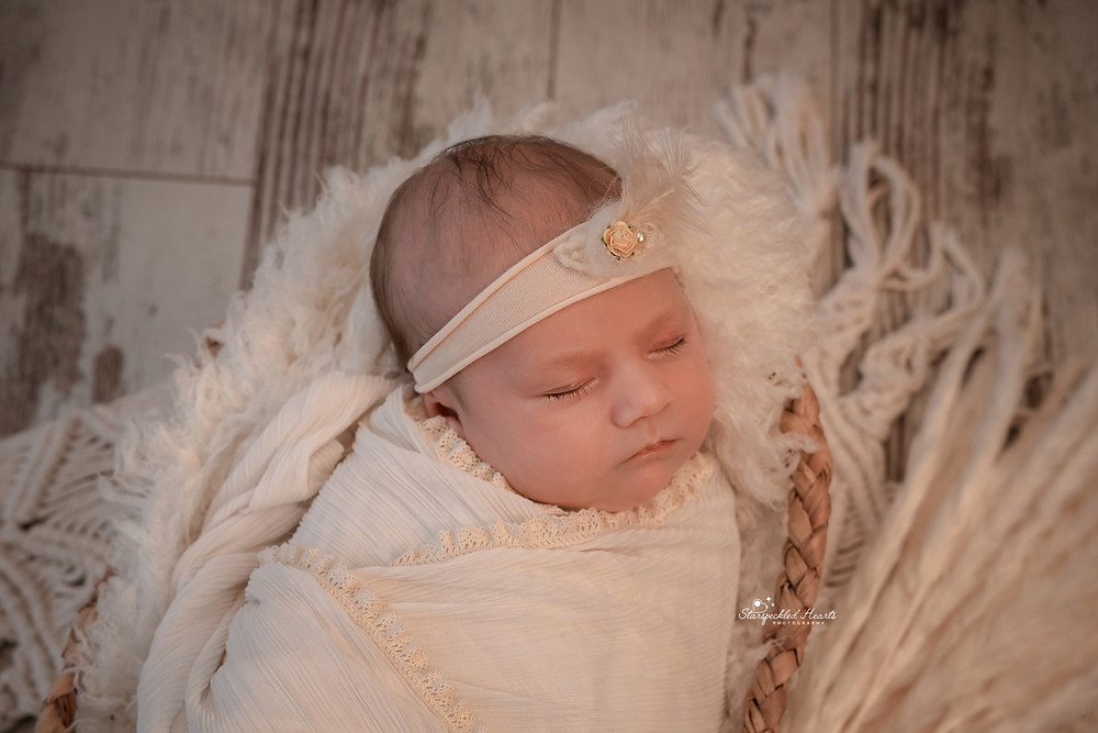 sleeping newborn wearing a feather headband and a ribbed white swaddle with lace trim, lying in a wicker basket for her newborn photoshoot in aldershot