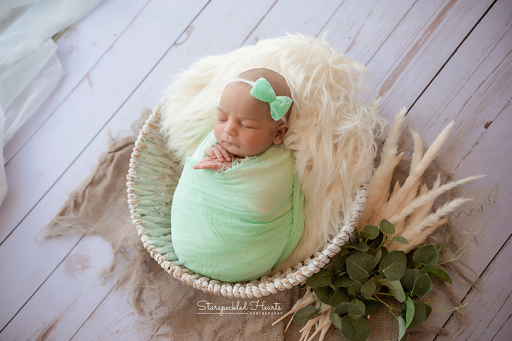 sleeping newborn baby girl swaddled in green for her newborn photography session in hampshire