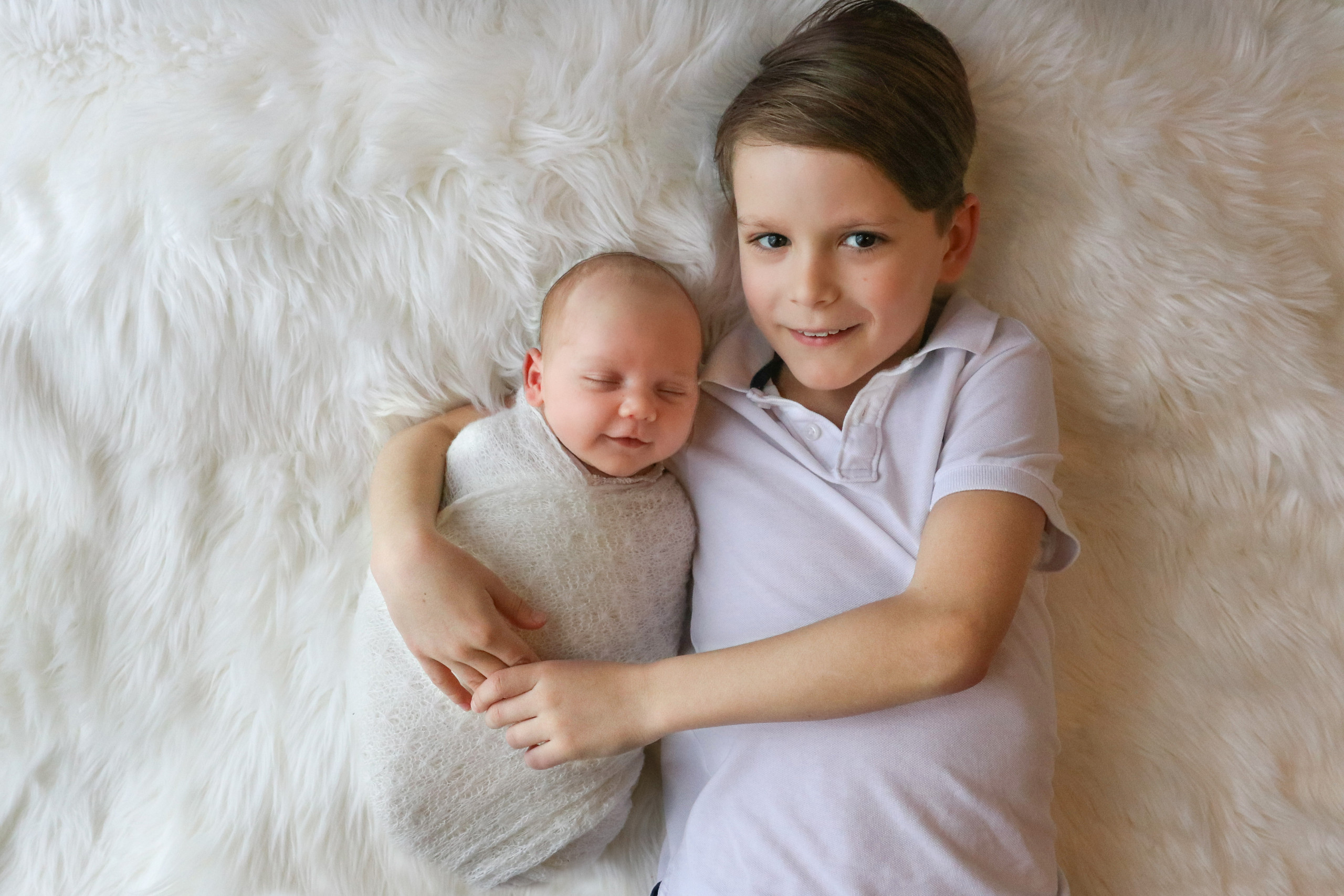 a smiling newborn boy wrapped in white, cuddled up with his smiling older brother