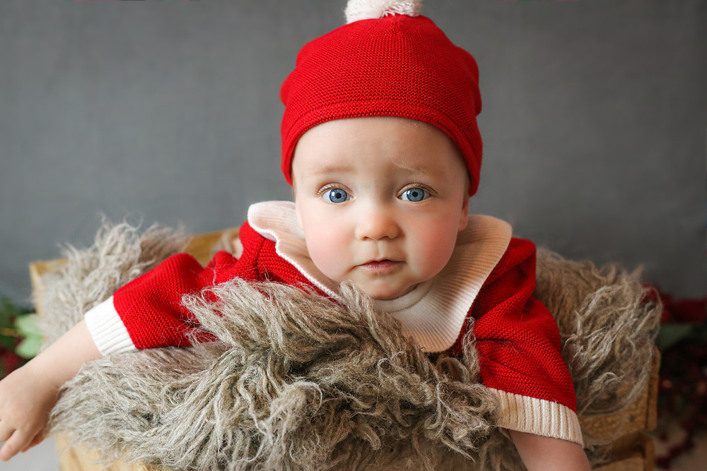 smiling baby boy wearing santa hat and a red christmas romper, lying in a crate with a grey fluffy rug