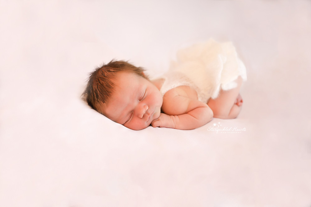 gorgeous newborn baby girl lying on her tummy wearing a white fluffy romper