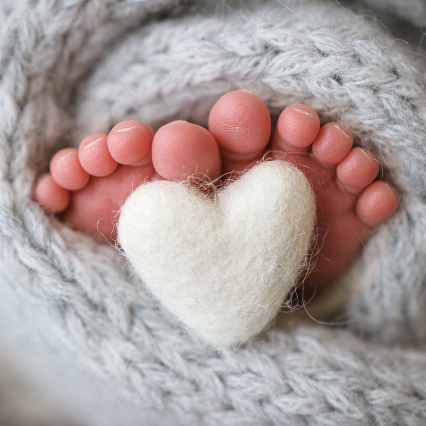 cute little baby toes holding up a felted heart