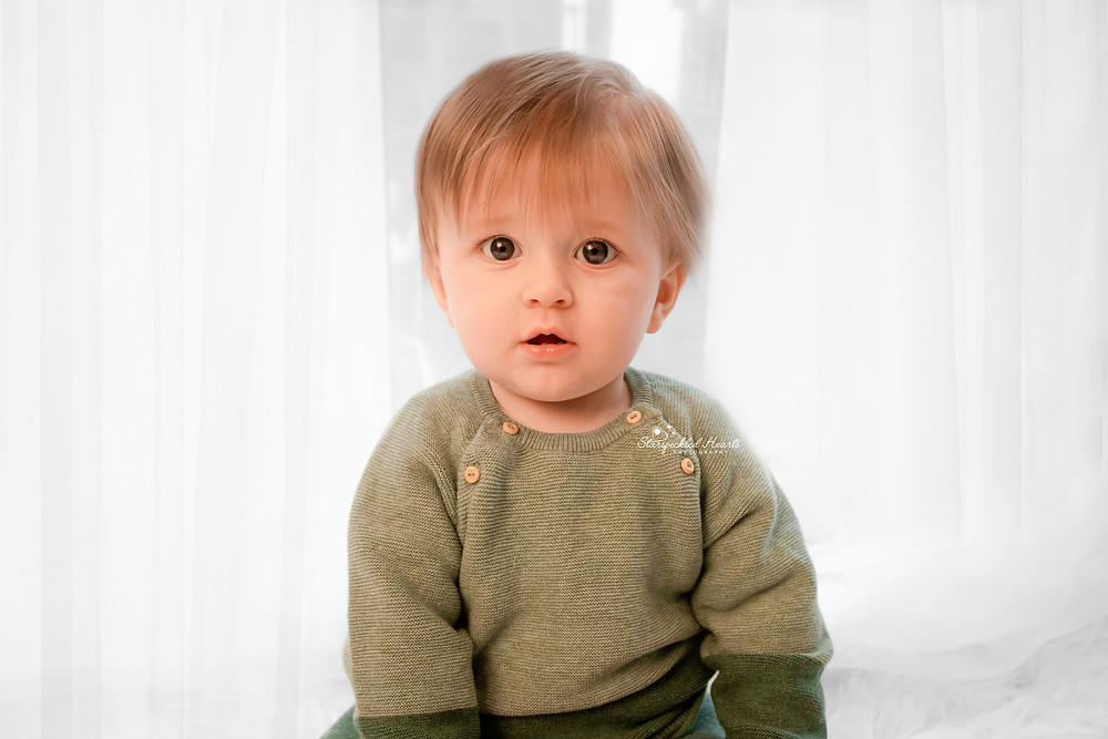 cute baby boy wearing a green knitted jumper for his baby photography session in hampshire