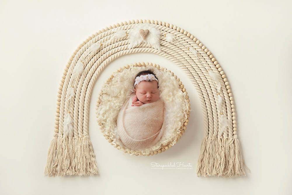 newborn baby girl lying in a basket with a macrame rainbow above her head for her newborn photoshoot in farnham hampshire