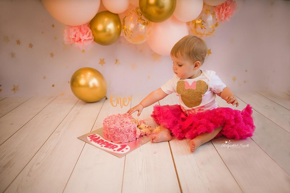 baby girl wearing a pink tutu sitting next to a pink cake