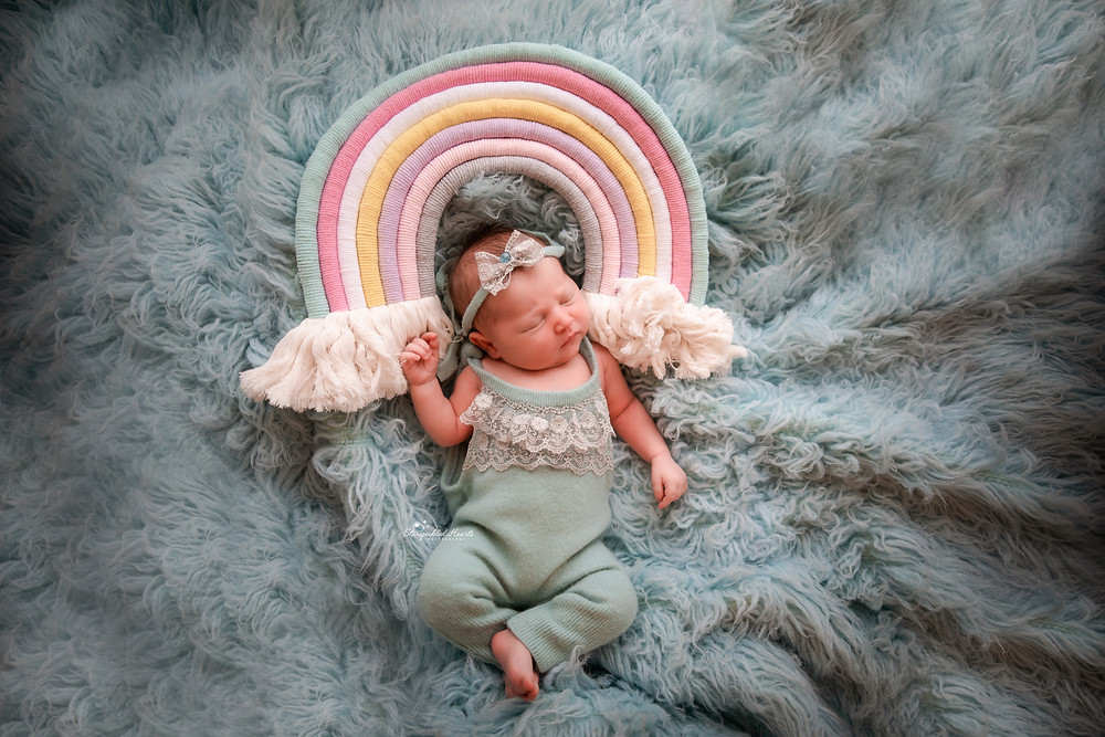 sweet newborn girl lying on a blue rug with a macrame rainbow over her head, wearing a blue long legged romper suit
