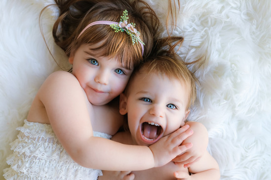 beautiful smiling toddler girl and a baby boy with arms around eachother, laying down on a white rug