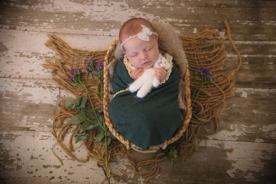 beautiful newborn baby girl wearing a teal wrap, laying in an oval wicker basket, cuddling a white teddy